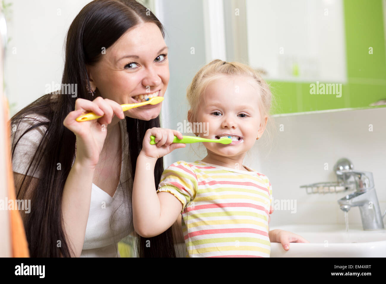 happy mother and daughter kid girl brushing teeth together Stock Photo