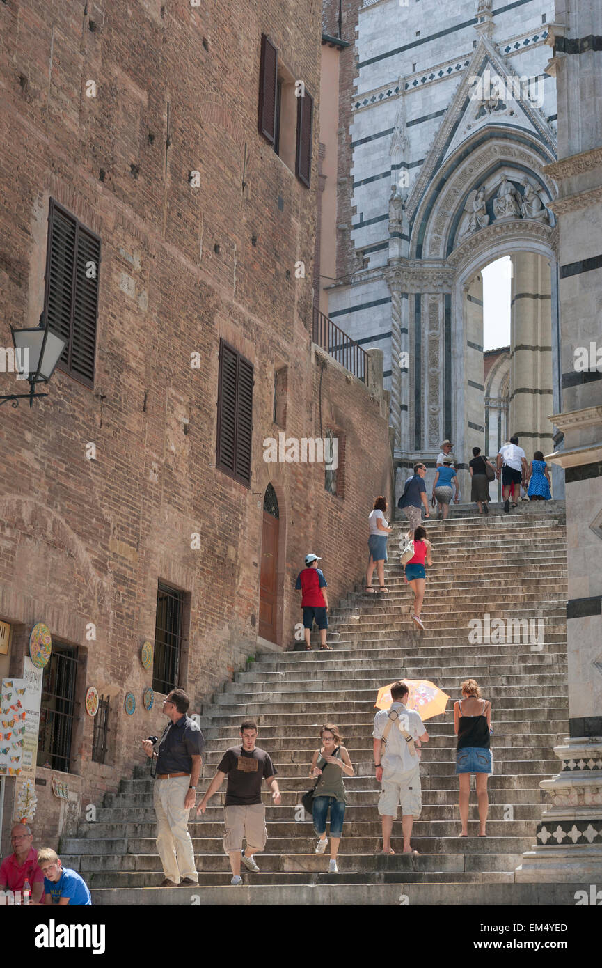 Italy tourism, view in summer of tourists ascending the stairway to the west end of the Duomo (cathedral) in Siena, Stock Photo