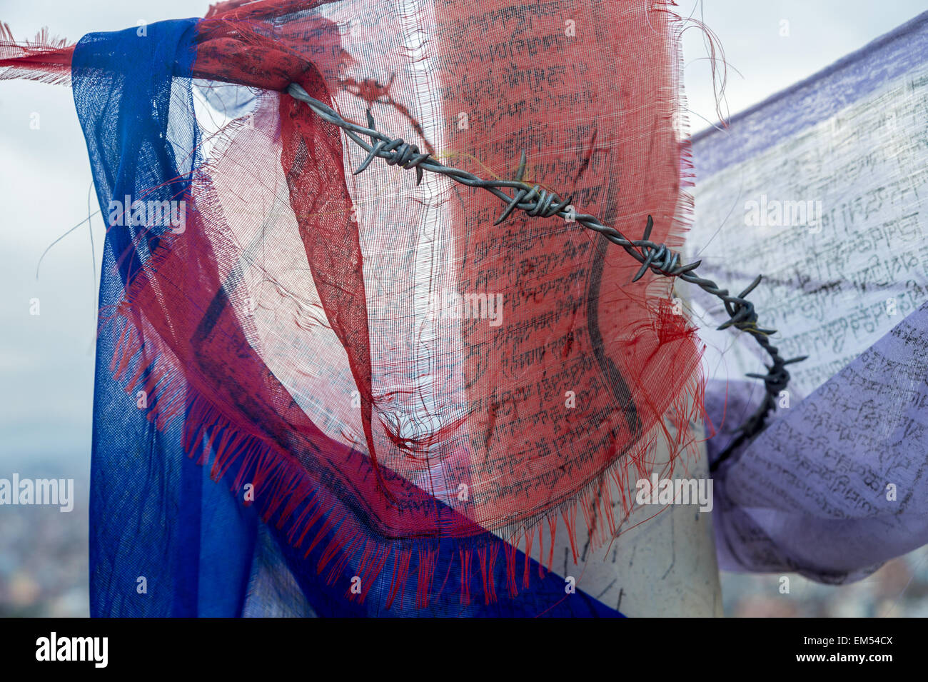 Close-up of prayer flags and barb wires. Perfect image to symbolise Tibet oppression. - Stock Image