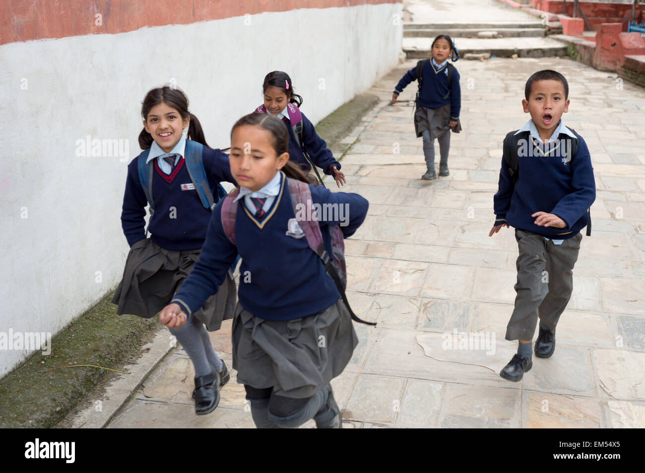 A group of children running back home after school - Stock Image