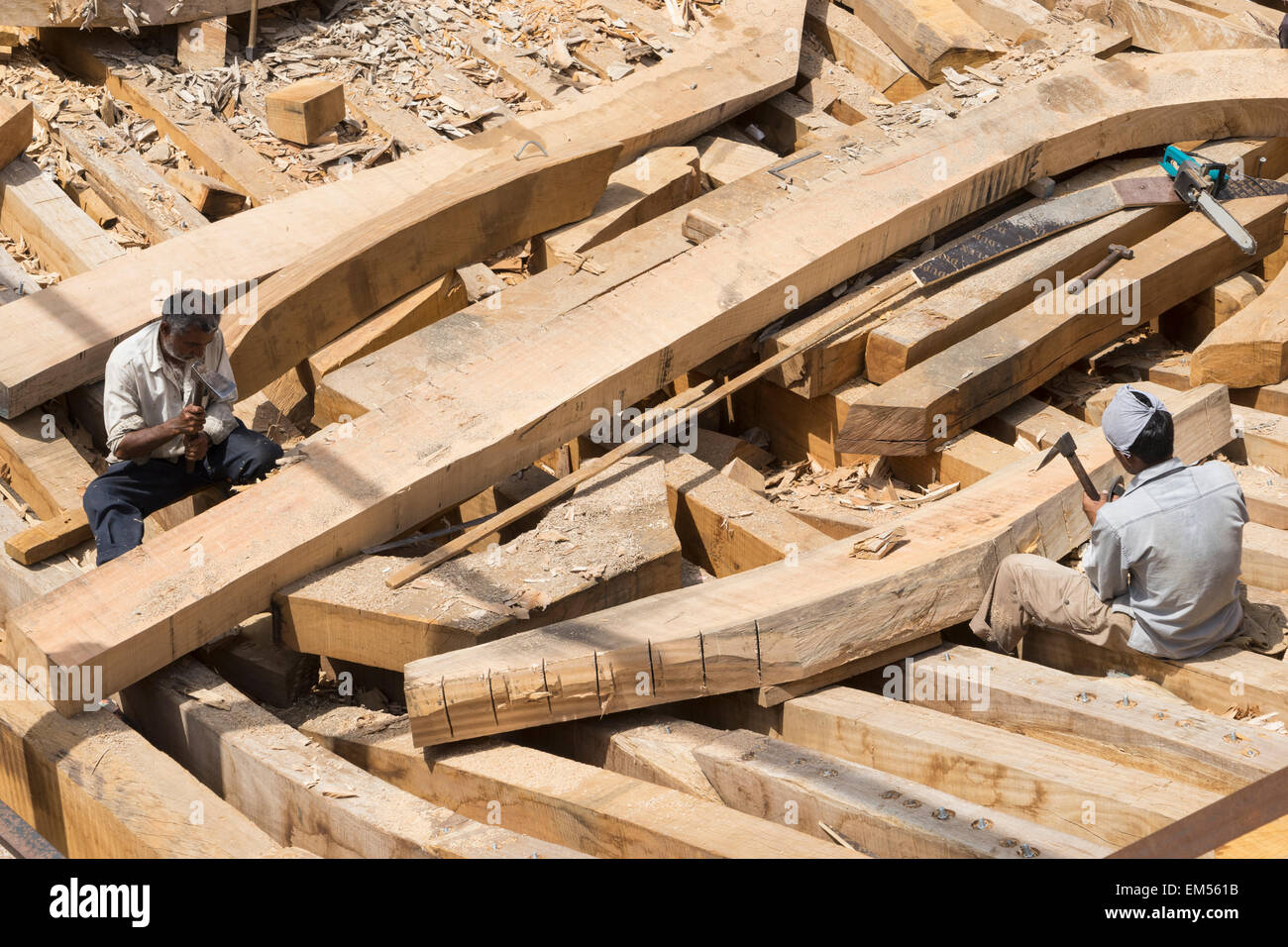 Building a traditional wooden dhow cargo ship in shipyard beside The Creek River in Dubai United Arab Emirates - Stock Image