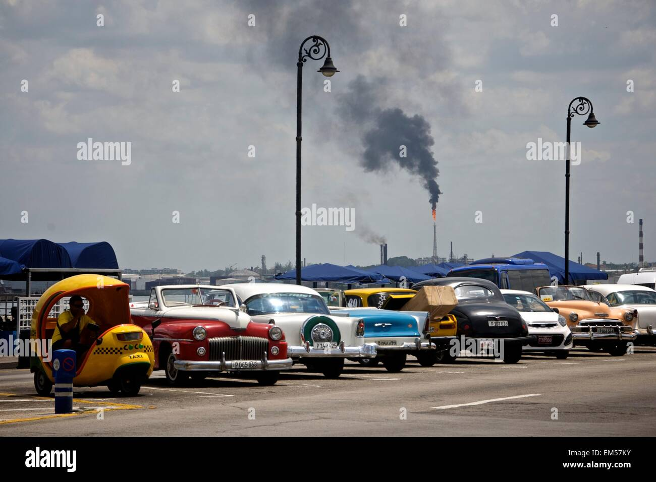 Classic American cars on a Cuban street in Havana with an oil refinery flare stack in the distance. - Stock Image