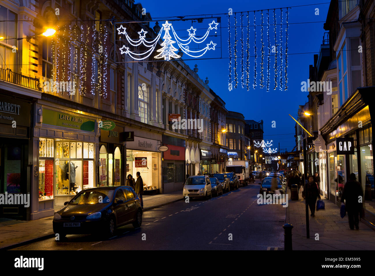 UK, England, Yorkshire, Harrogate at Christmas, James Street, lights above shops at dusk - Stock Image