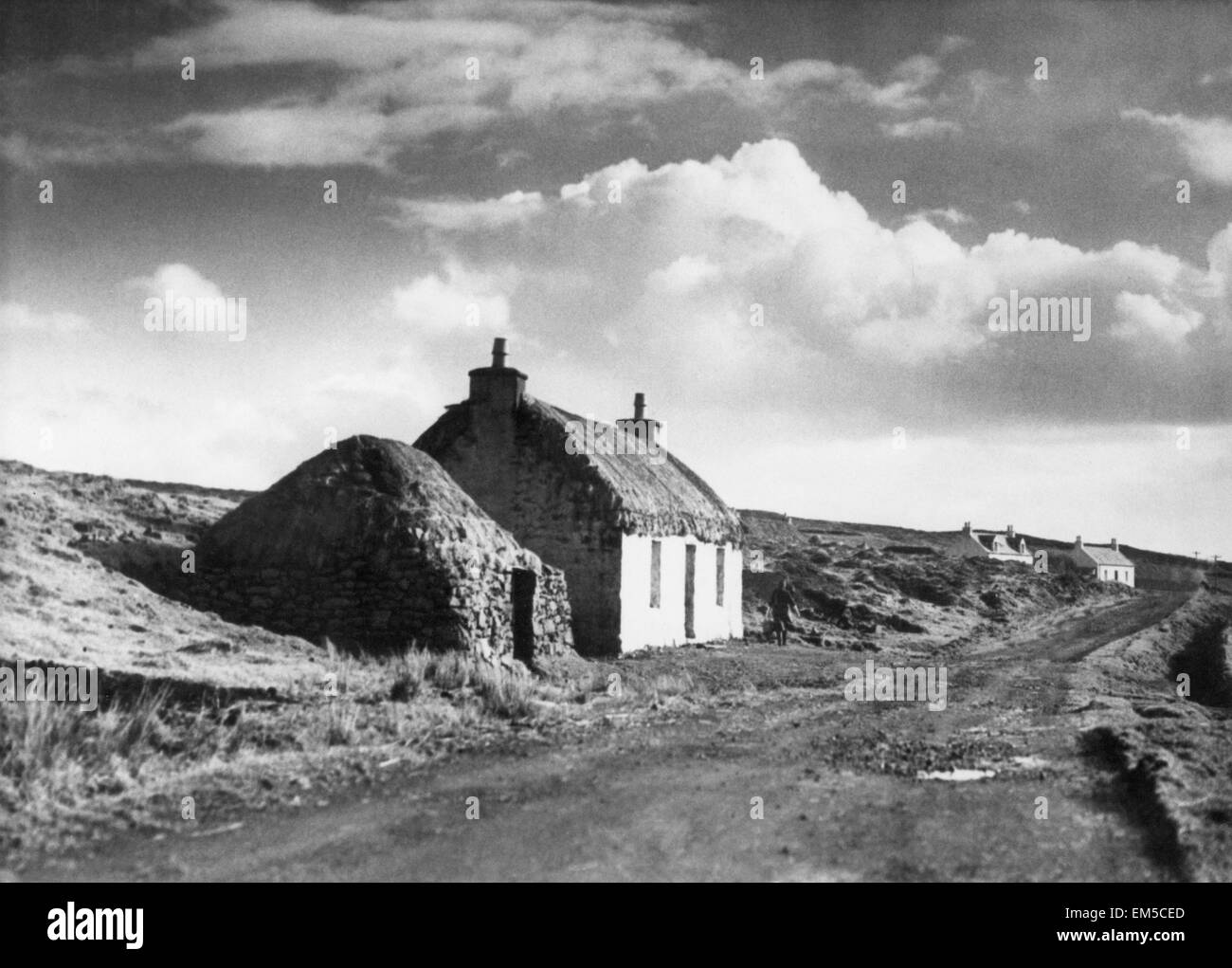 Near Dunvegan, Isle of Skye, Scotland, a typical view Housing Cottage Lane Thatched roof Clouds Scenic Country Scene - Stock Image