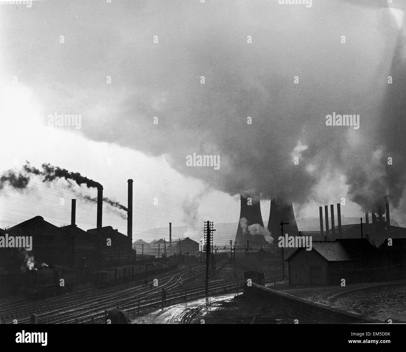Cooling towers and smoking chimneys pollute the air at a Sheffield industrial site Circa 1947 - Stock Image