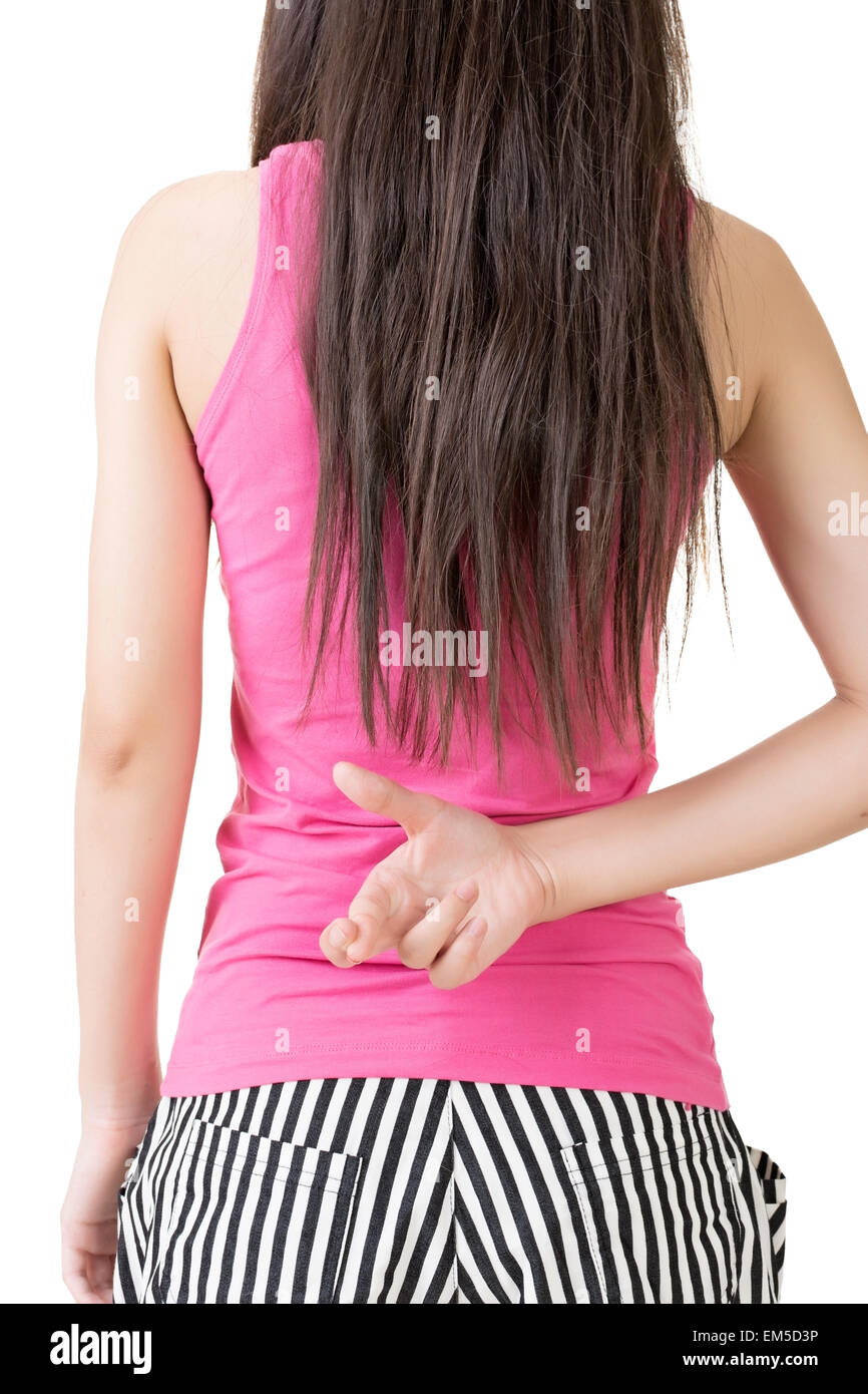 Young asian woman keeps fingers crossed behind her back - Stock Image