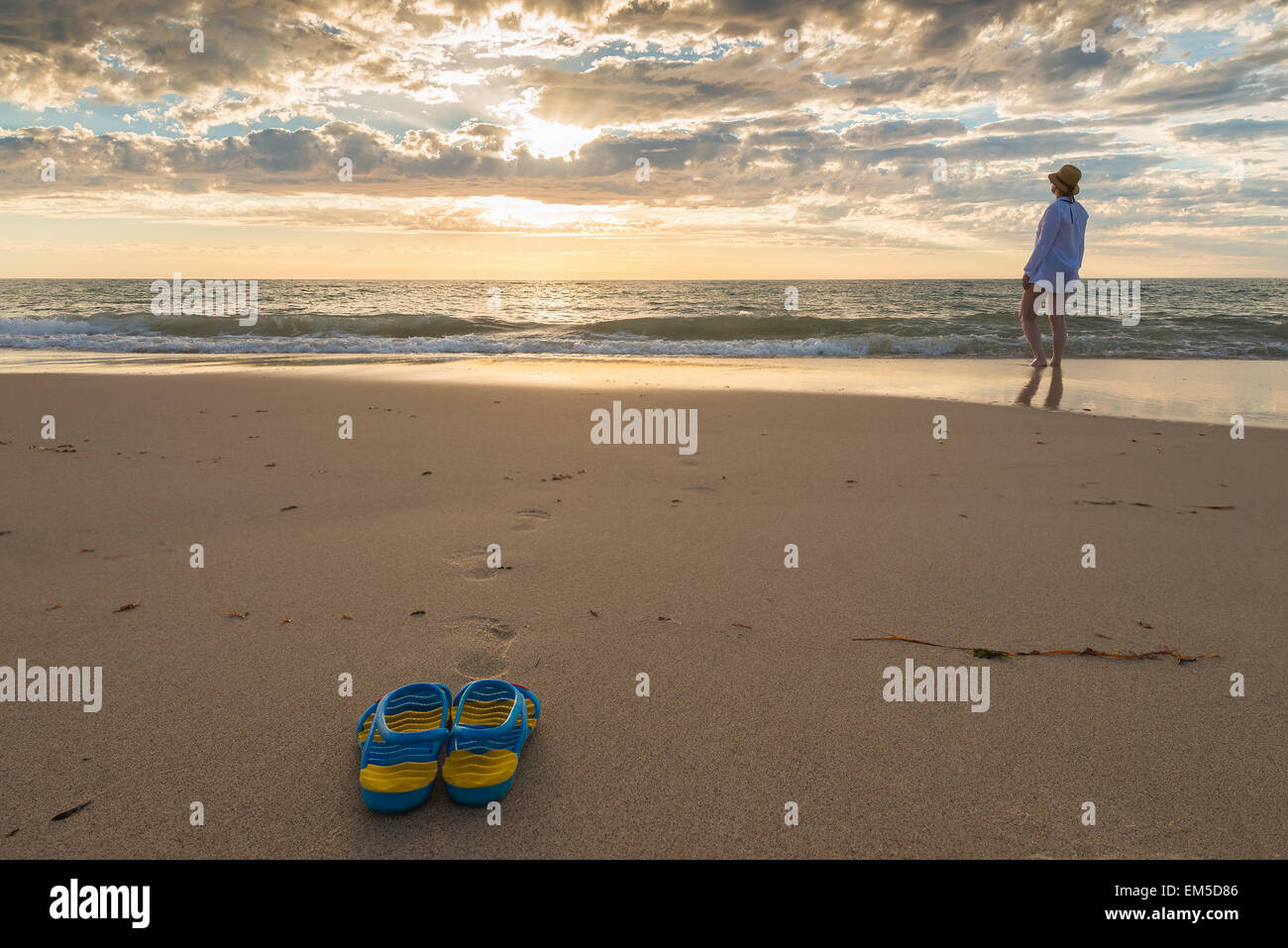 Woman took off her shoes and went closer to the sea at sunset - Stock Image