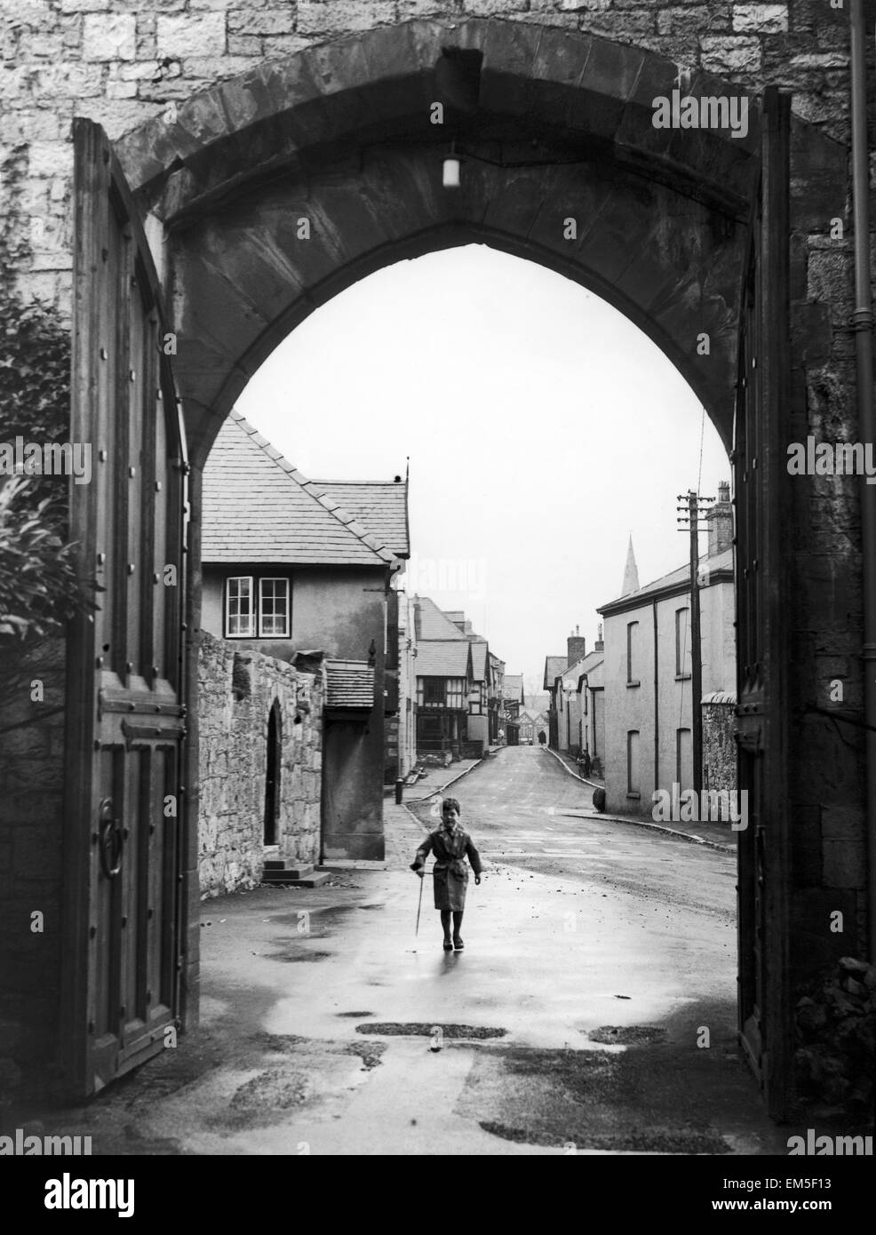 A small boy walks through the archway at the entrance of Ruthin Castle Denbighshire February 1944 - Stock Image