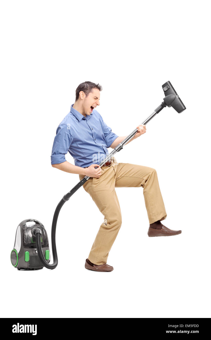 Full length portrait of a silly young man imagining that he plays guitar on a vacuum cleaner isolated on white background - Stock Image