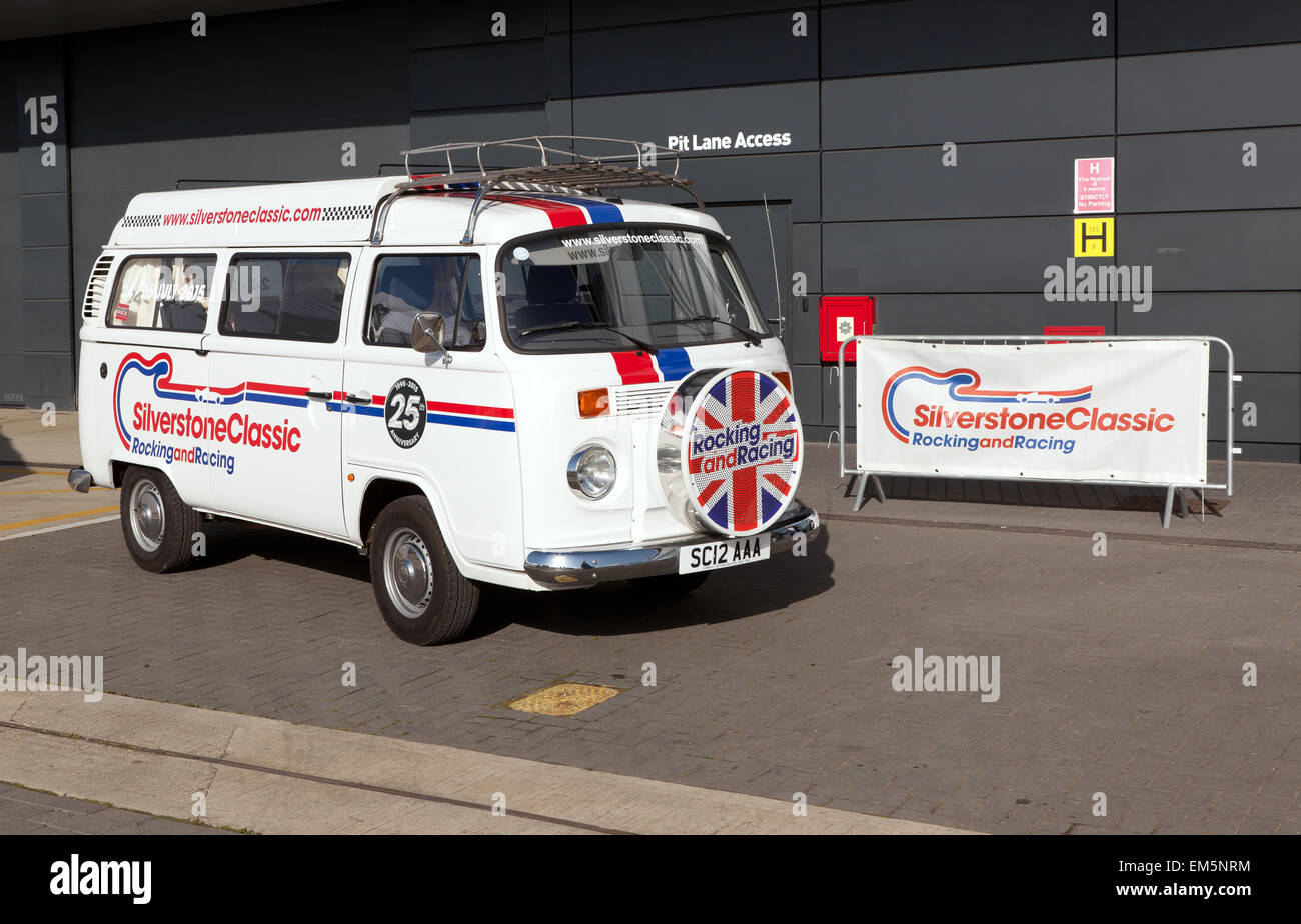 A classic VW microbus advertising the 2015 Silver Anniversary Silverstone Classic outside the pit area of the Silverstone - Stock Image