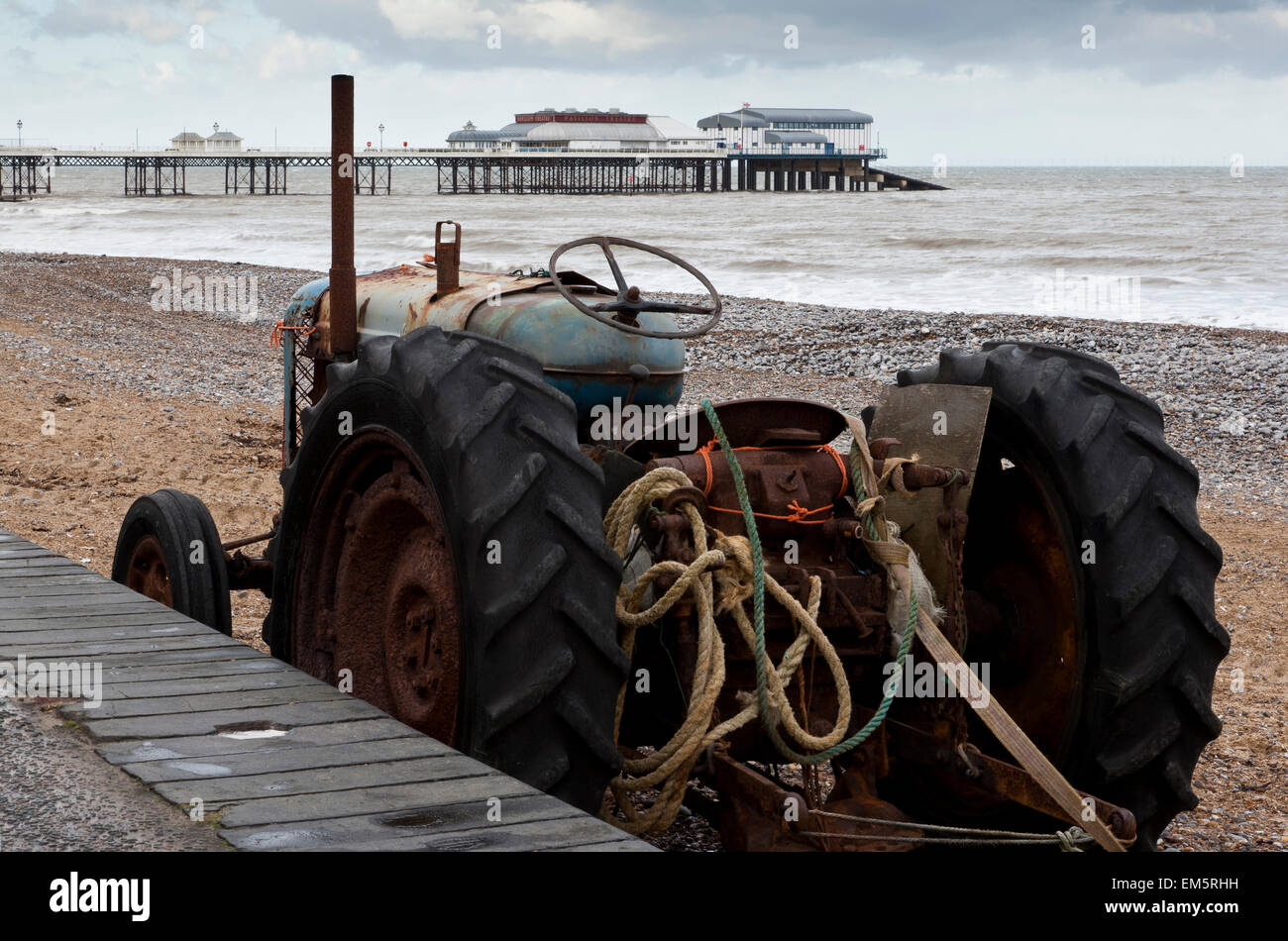 An old vintage tractor used in the fishing industry standing on the beach at Cromer, Norfolk UK - Stock Image