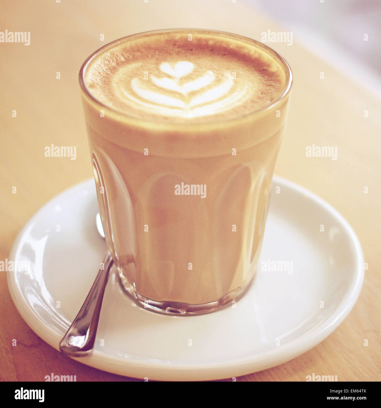 Cup of art latte or cappuccino coffee with retro filter effect - Stock Image