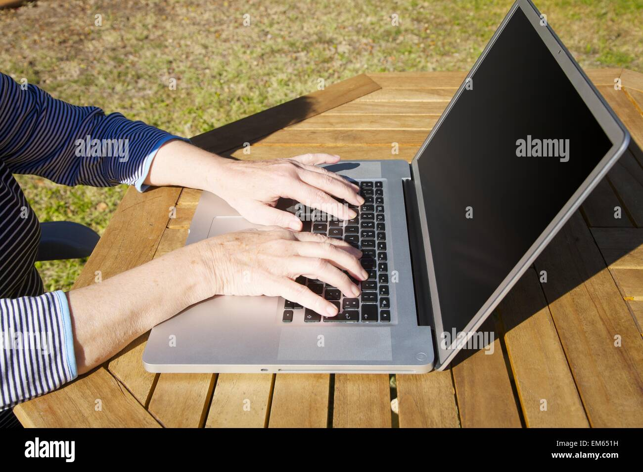 hands of old woman typing on laptop - Stock Image