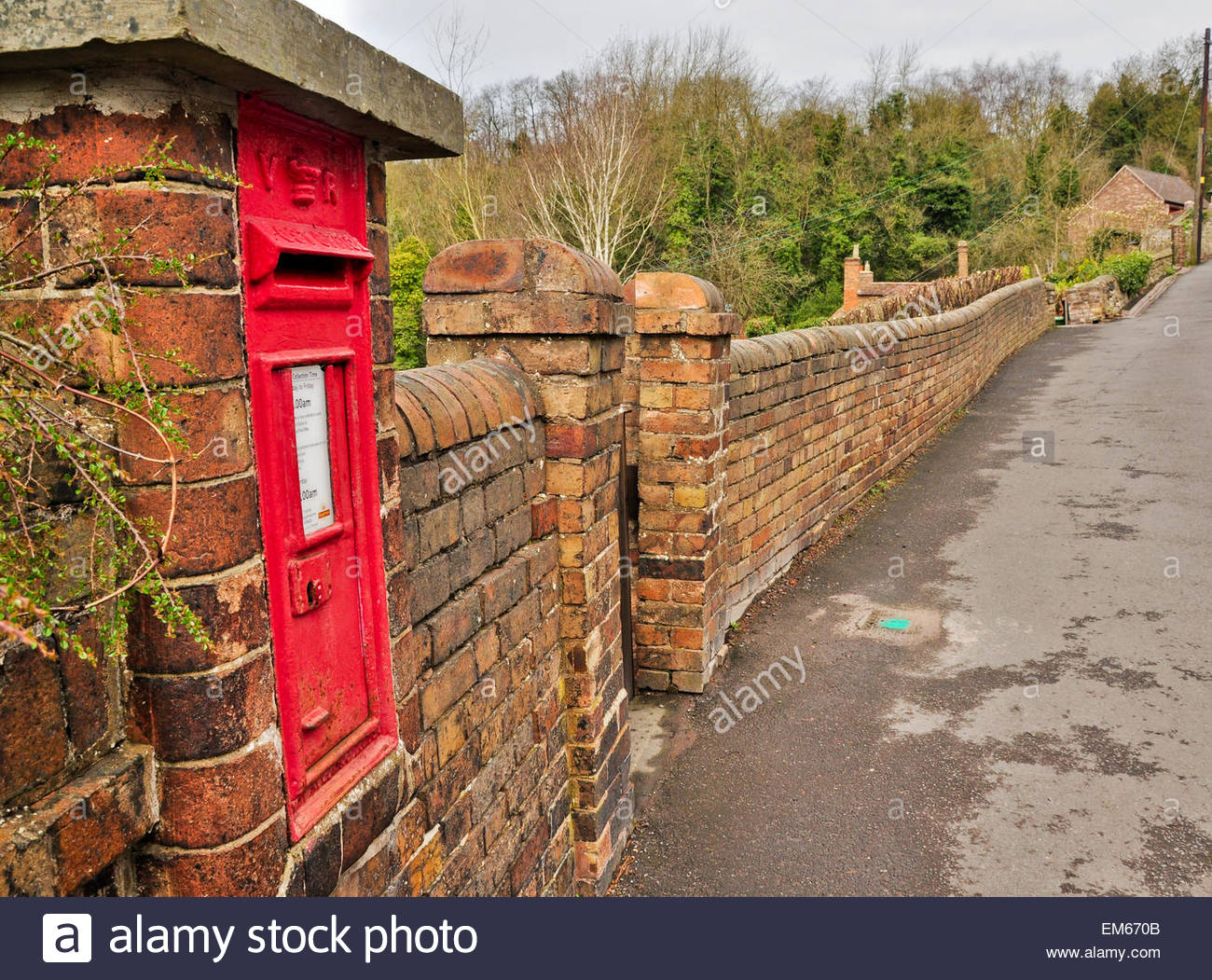 A red post box in a brick wall on a country lane in Ironbridge, Shropshire, UK - Stock Image