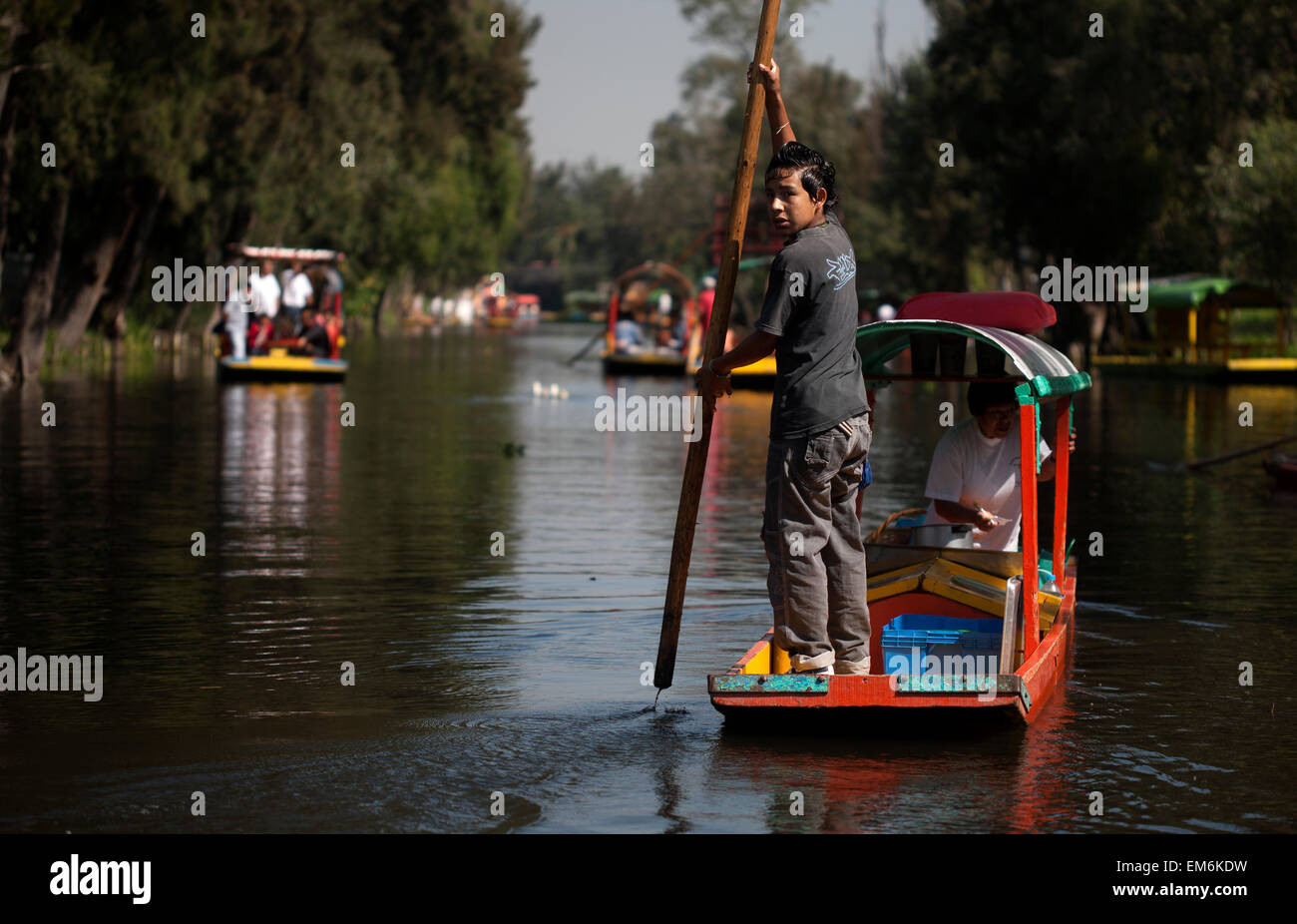 An boy uses a pole to navigate his boat through a canal in Xochimilco on the south side of Mexico City - Stock Image