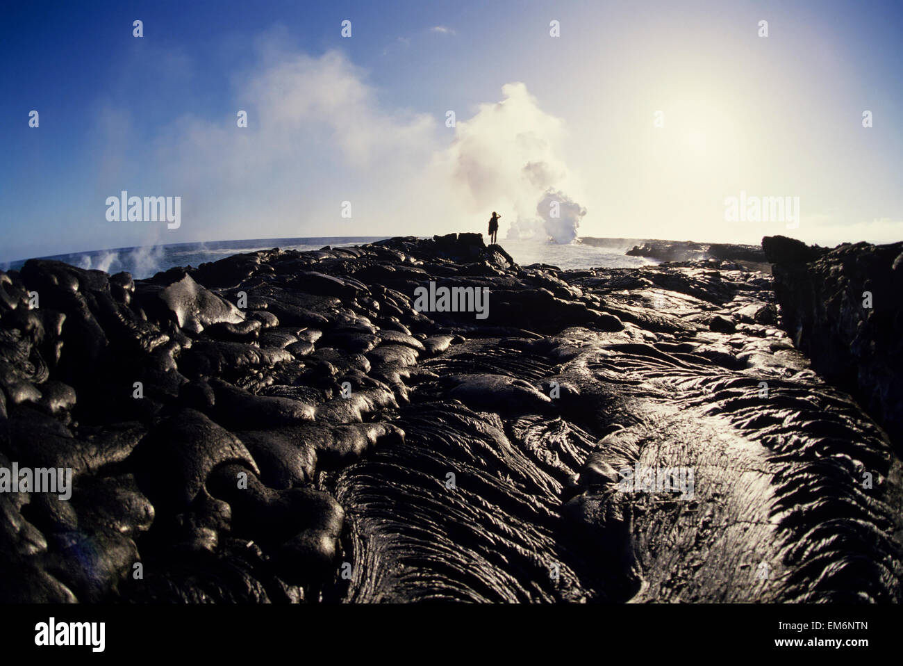 Hawaii, Big Island, Hawaii Volcanoes National Park, East Rift Zone, Person Observing Lava Flow Into Ocean In Distance. - Stock Image