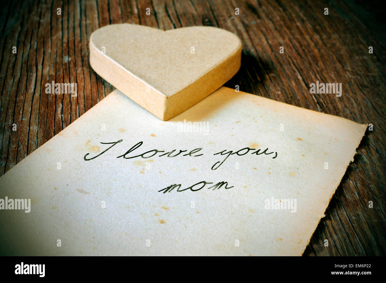 a cardboard heart and and old sheet of paper with the text I love you mom written in it on a rustic wooden table, - Stock Image