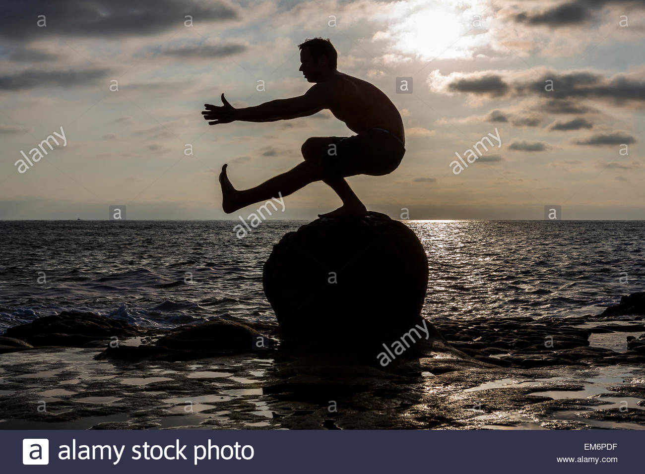 The silhouette of a shirtless male CrossFit athlete as he performs a pistol or one-legged squat on a rock in the - Stock Image