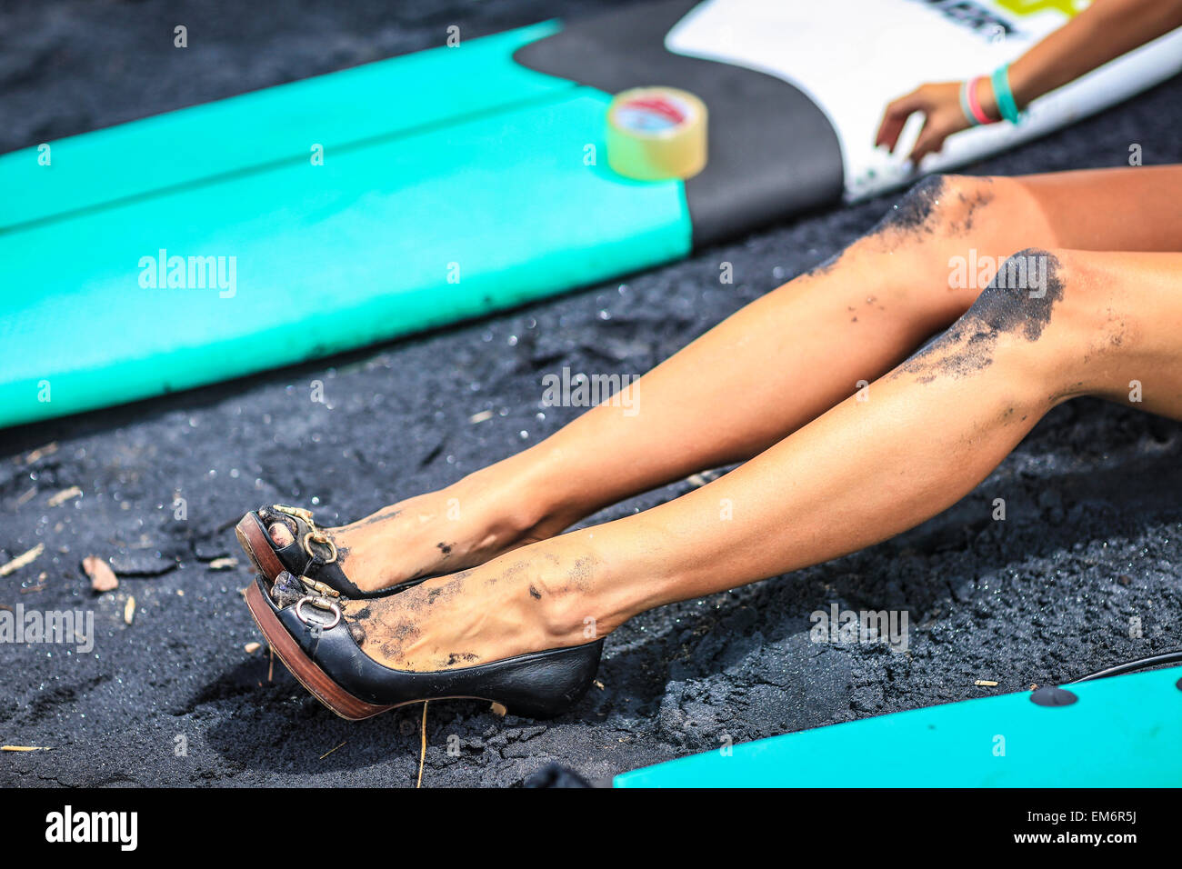 Surfer girls catch waves in high heels. - Stock Image