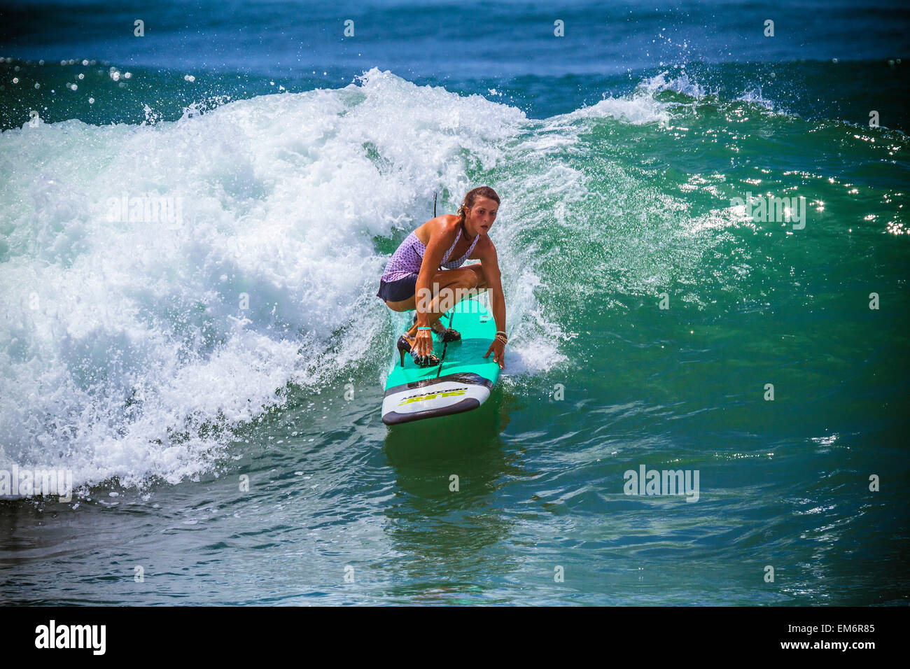 Surfer girl catches wave in high heels. - Stock Image