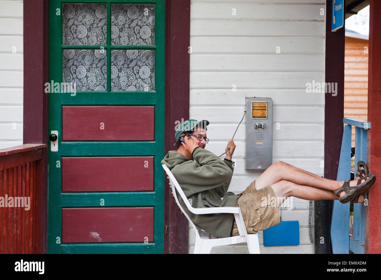 A young man leans back in a chair as he talks on a public phone on a porch in McCarthy, Alaska. - Stock Image