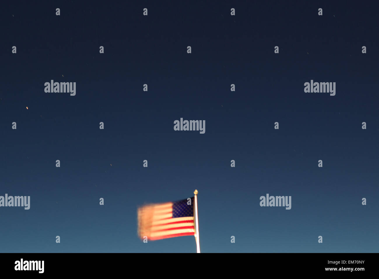 A photograph of an American flag blowing in the wind. The photograph was taken at night time with a long exposure. Stock Photo