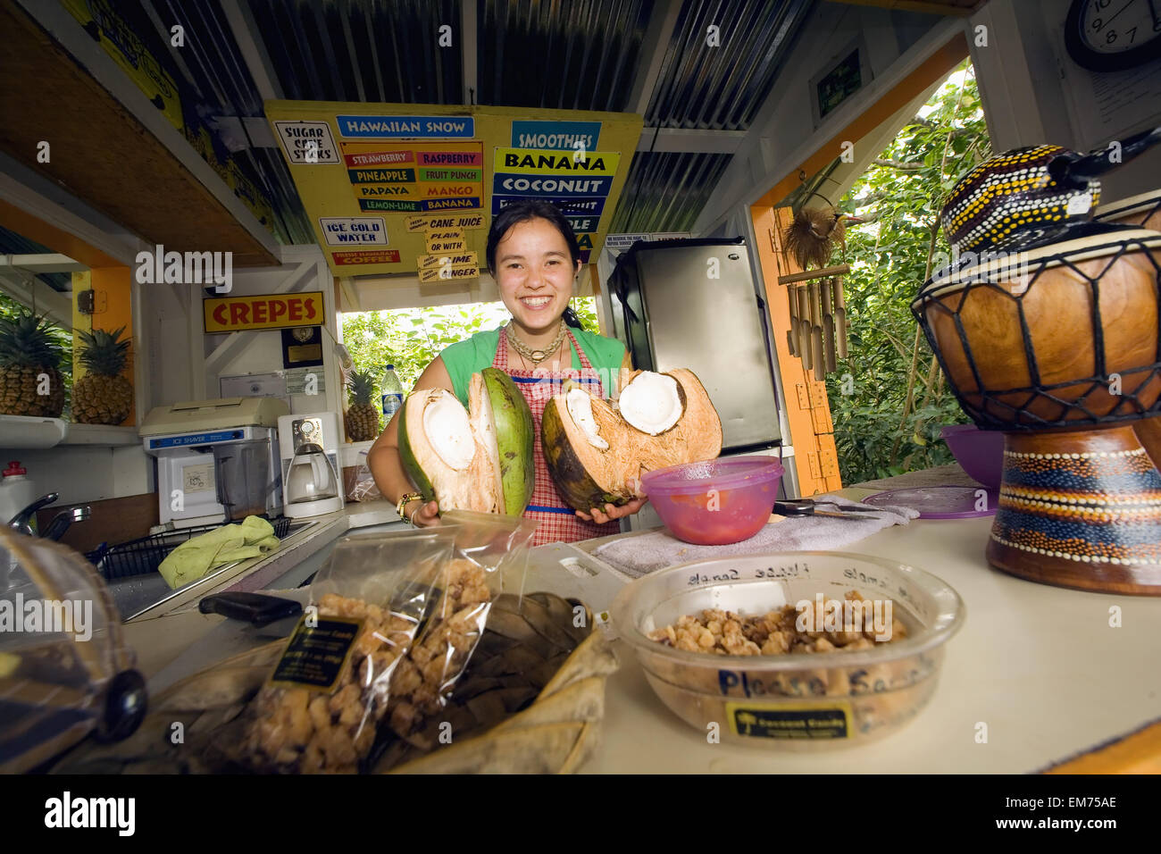 Hawaii, Maui, Hana, Fruit And Souvenir Stand At Huelo Lookout, Girl Holding Coconuts Behind The Counter. Stock Photo