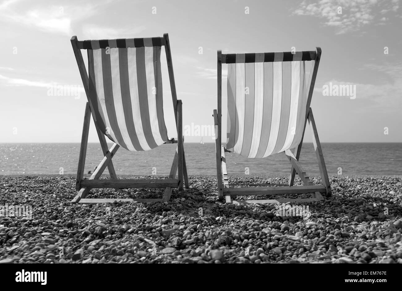 Brighton Beach, Deck chairs on the beach with single sailing boat in the background black and white - Stock Image