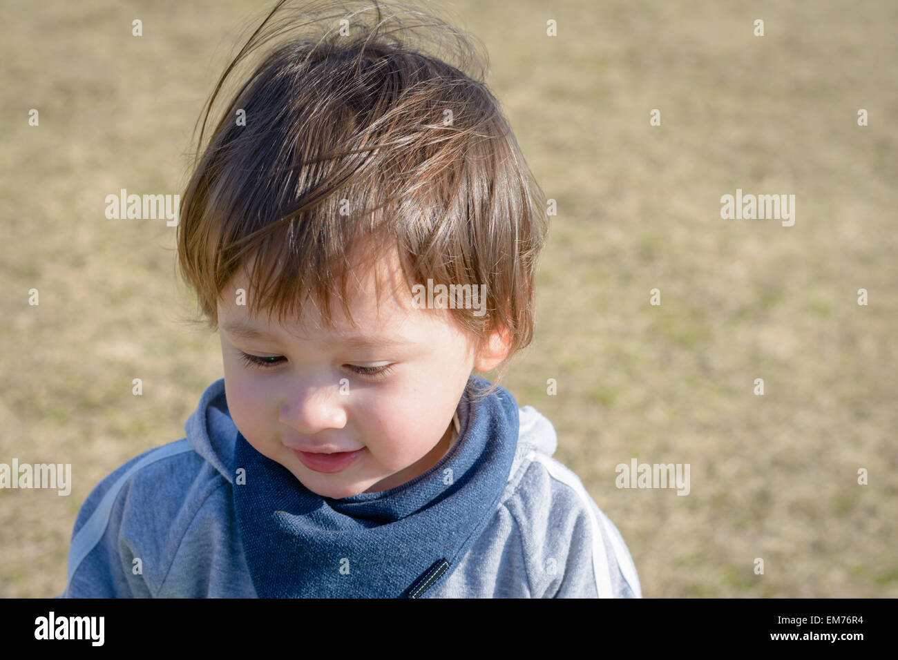 A 2 year old boy at a playground. - Stock Image