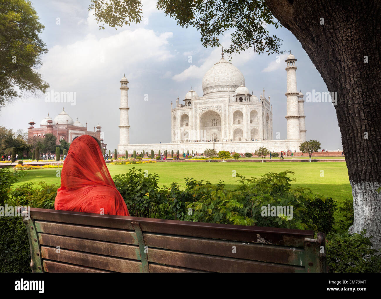 Woman in red scarf sitting on the bench in the shadow and looking at Taj Mahal in Agra, Uttar Pradesh, India - Stock Image