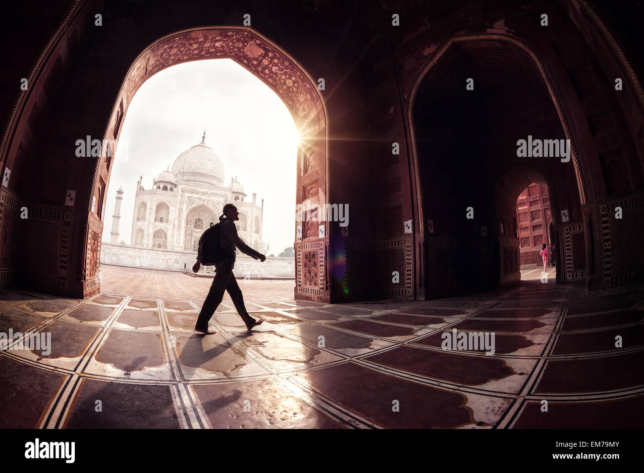 Tourist with backpack walking in the mosque arch near Taj Mahal in Agra, Uttar Pradesh, India - Stock Image