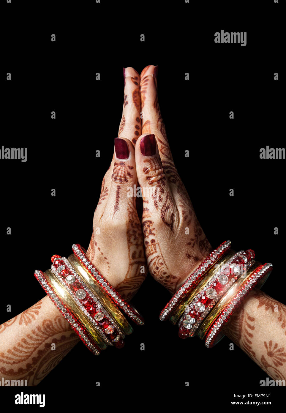 Woman hands with henna in Namaste mudra on black background - Stock Image