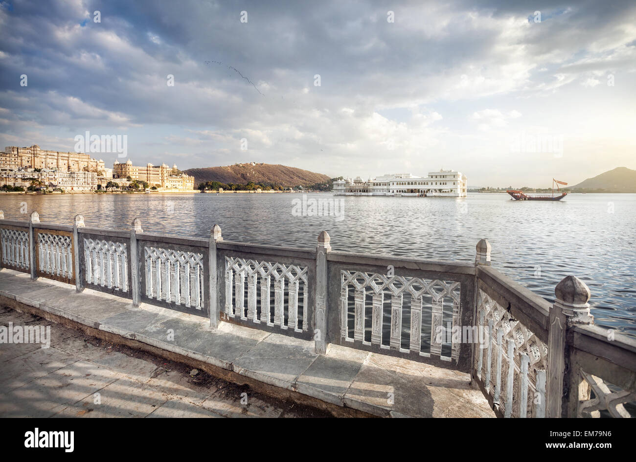 Lake Pichola with white palace in the center at cloudy sky in Udaipur, Rajasthan, India - Stock Image