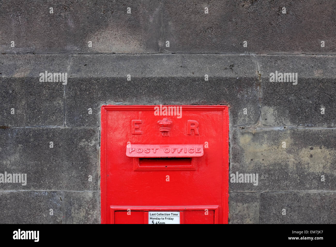 Red postbox in a grey wall in Winchester - Stock Image