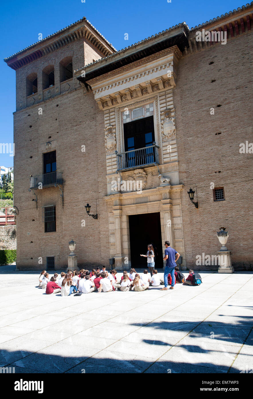 School children listen to their teacher on an educational visit to the historic sites of Granada, Spain - Stock Image