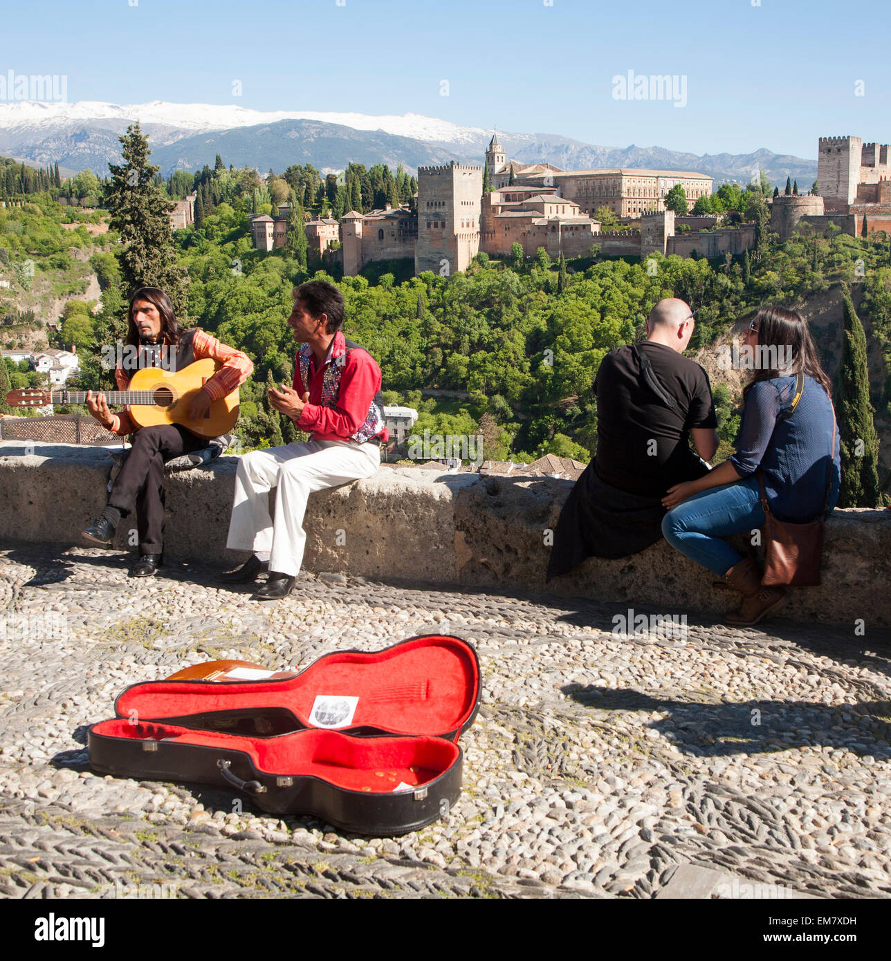 Flamenco musicians play with a backdrop of the snow Sierra Nevada mountains and the Alhambra, Granada, Spain - Stock Image