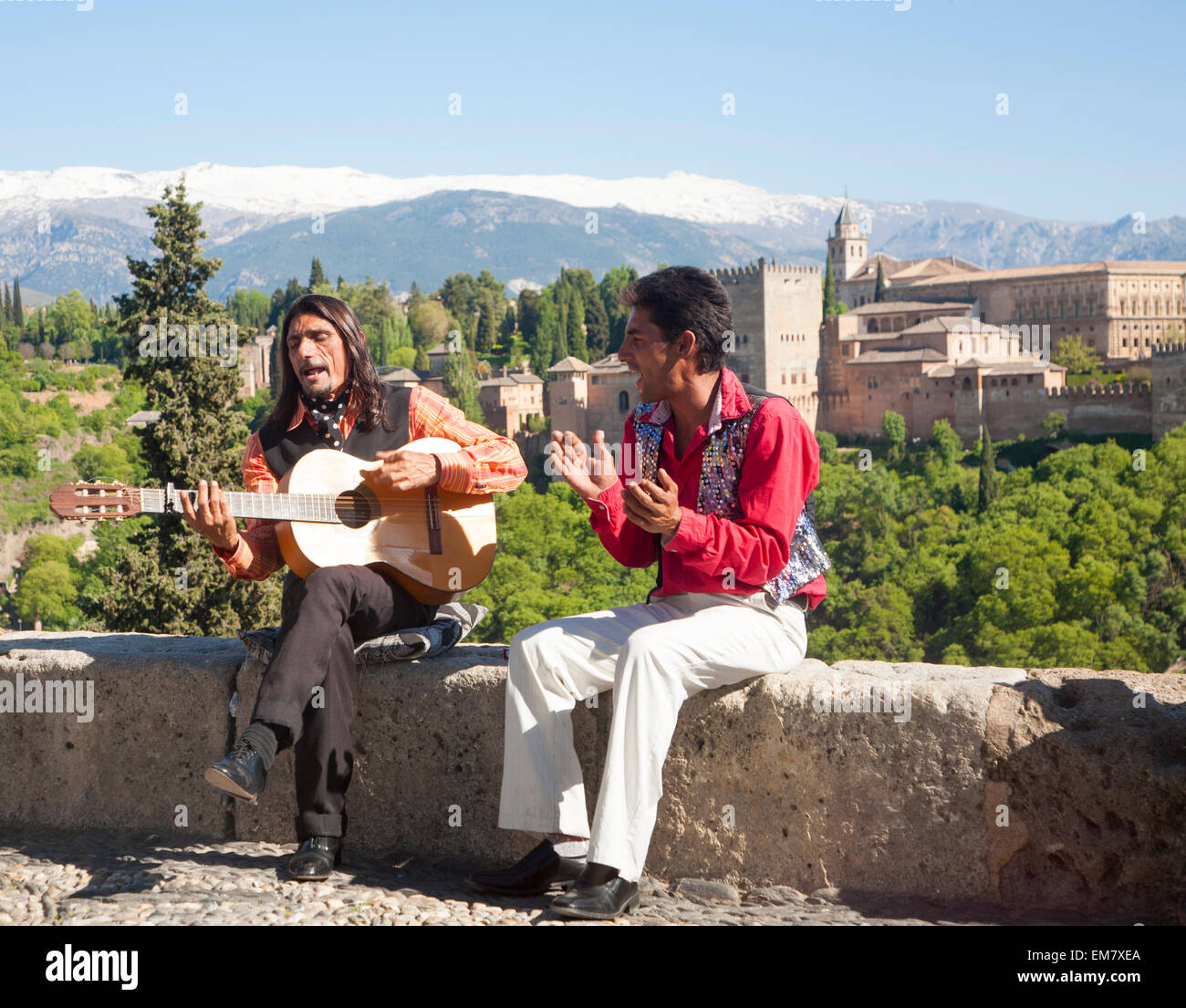 Flamenco musicians play with a backdrop of the Alhambra and snow topped Sierra Nevada mountain, Granada, Spain - Stock Image