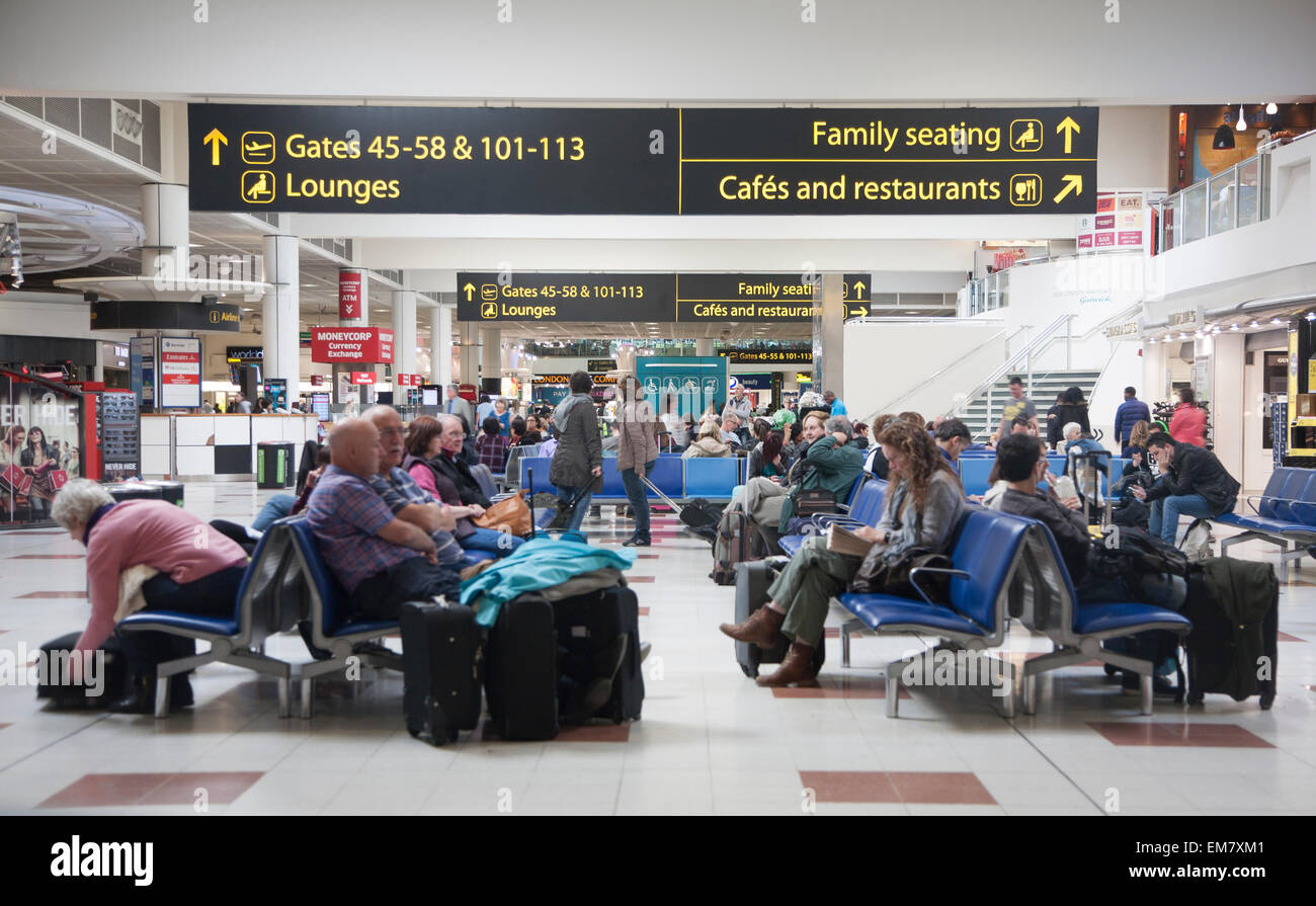 People waiting in departure lounge at Gatwick airport, England - Stock Image