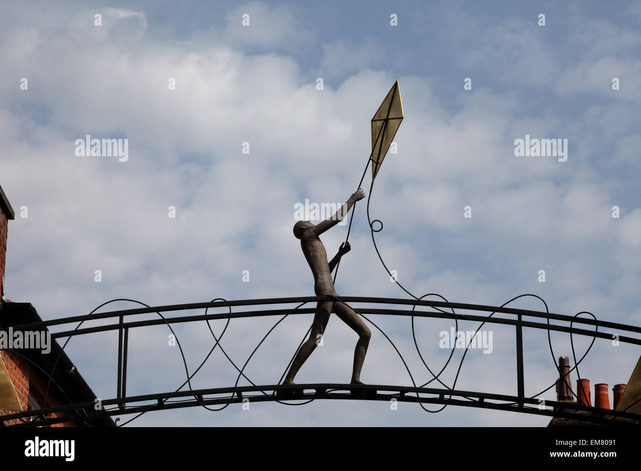 The Kite Flyer sculpture above Parchment Street in Winchester. A bronze figure of a man flying a kite - Stock Image