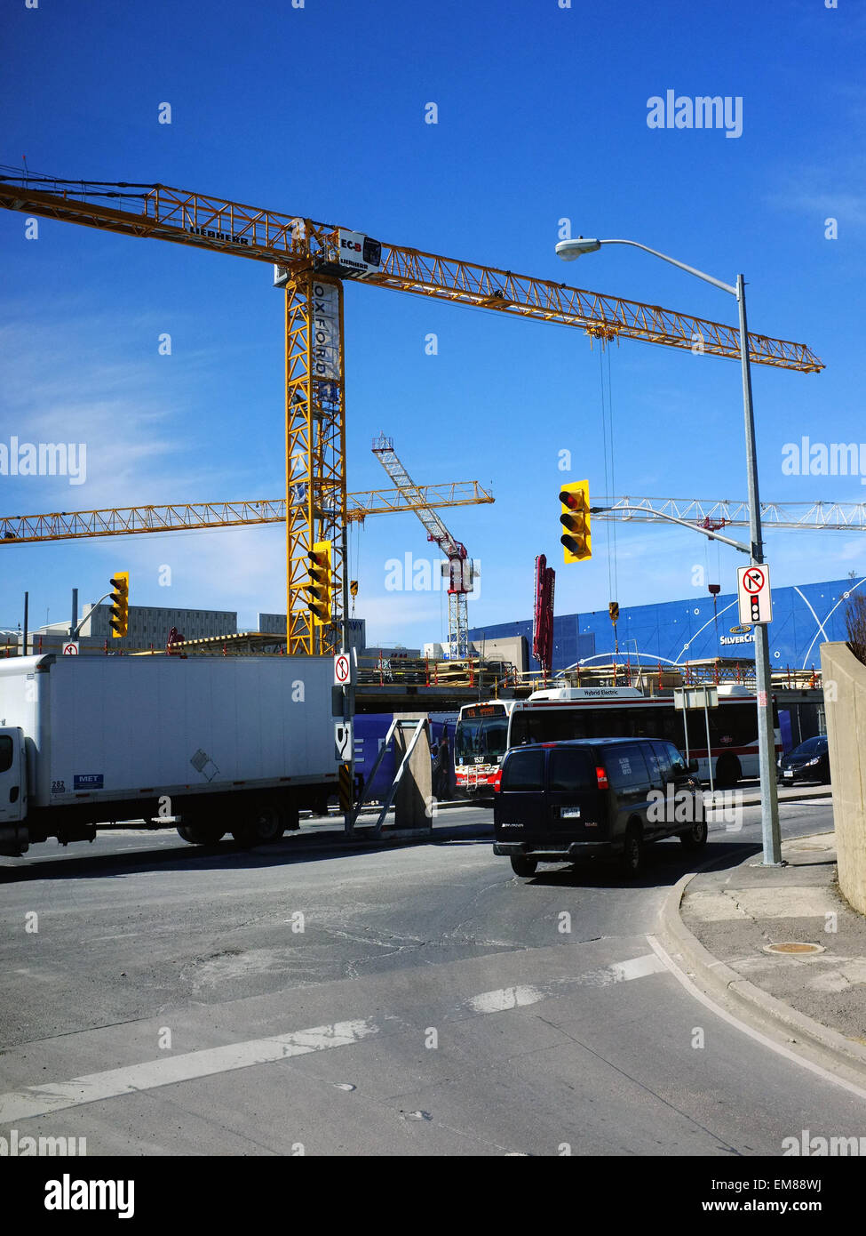 Cars drive past large tower cranes on the outskirts of Toronto in Canada. - Stock Image