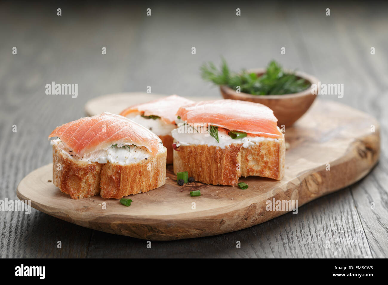 baguette slices with smoked salmon and cheese cream on wooden table - Stock Image