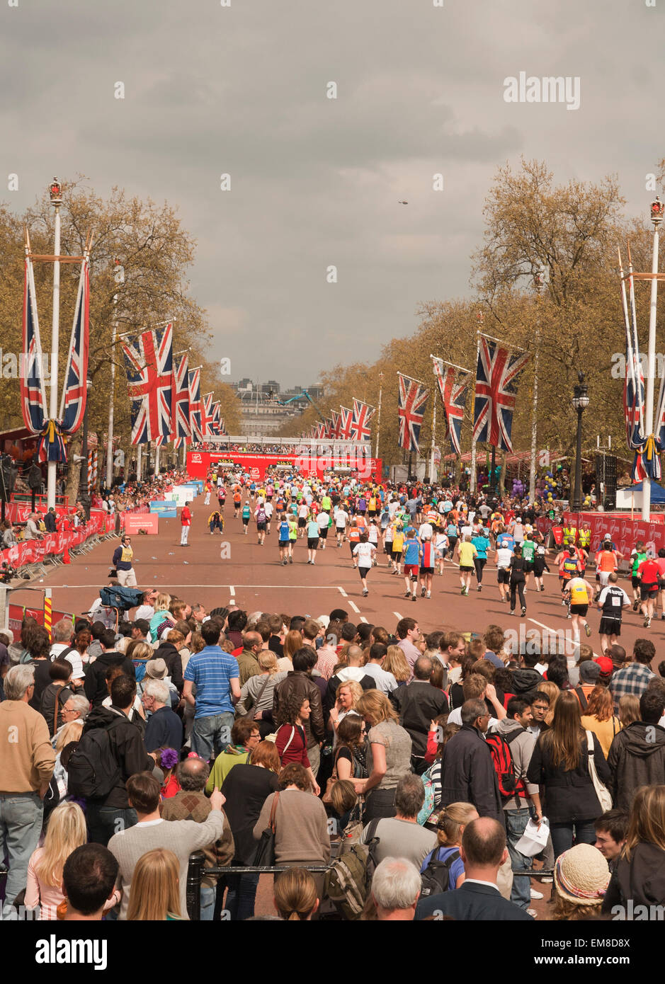 Marathon runners approach the finish line on Birdcage Walk during the London Marathon. - Stock Image