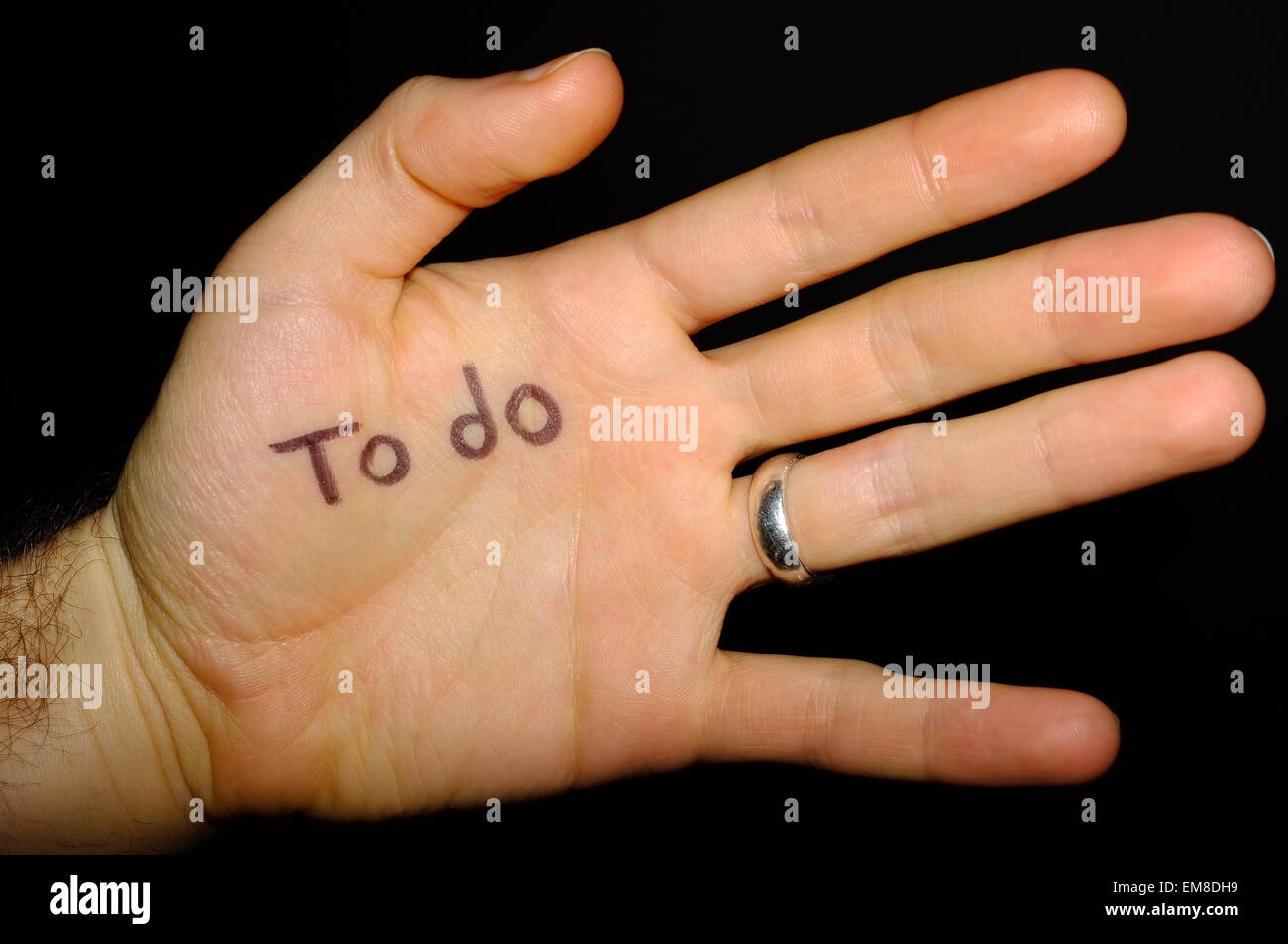To do written on the palm of a hand photographed against a black background. - Stock Image