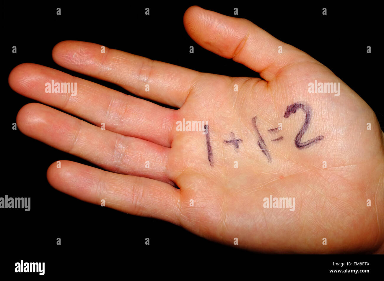 A simple maths sum written on the palm of a hand photographed against a black background. - Stock Image