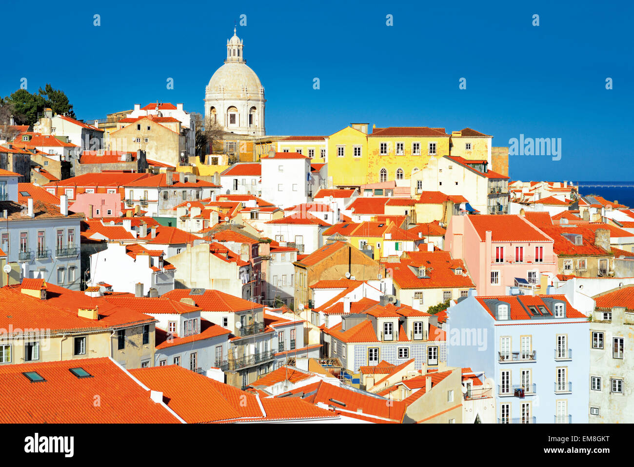 Portugal, Lisbon: View over the rooftops of old Lisbon and Tagus river from Miradouro Portas do Sol in Alfama - Stock Image