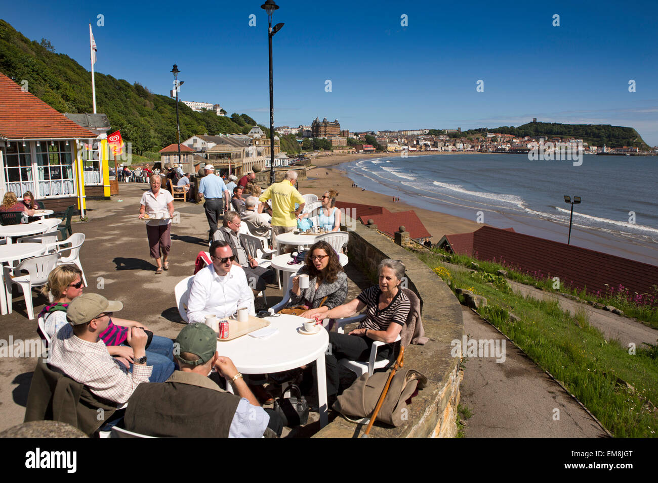 UK, England, Yorkshire, Scarborough, Clock Café, customers sitting outside above South Sands - Stock Image