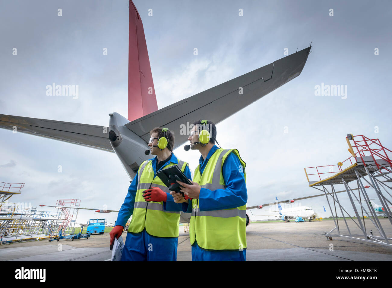 Airside engineers inspecting jet aircraft on runway - Stock Image