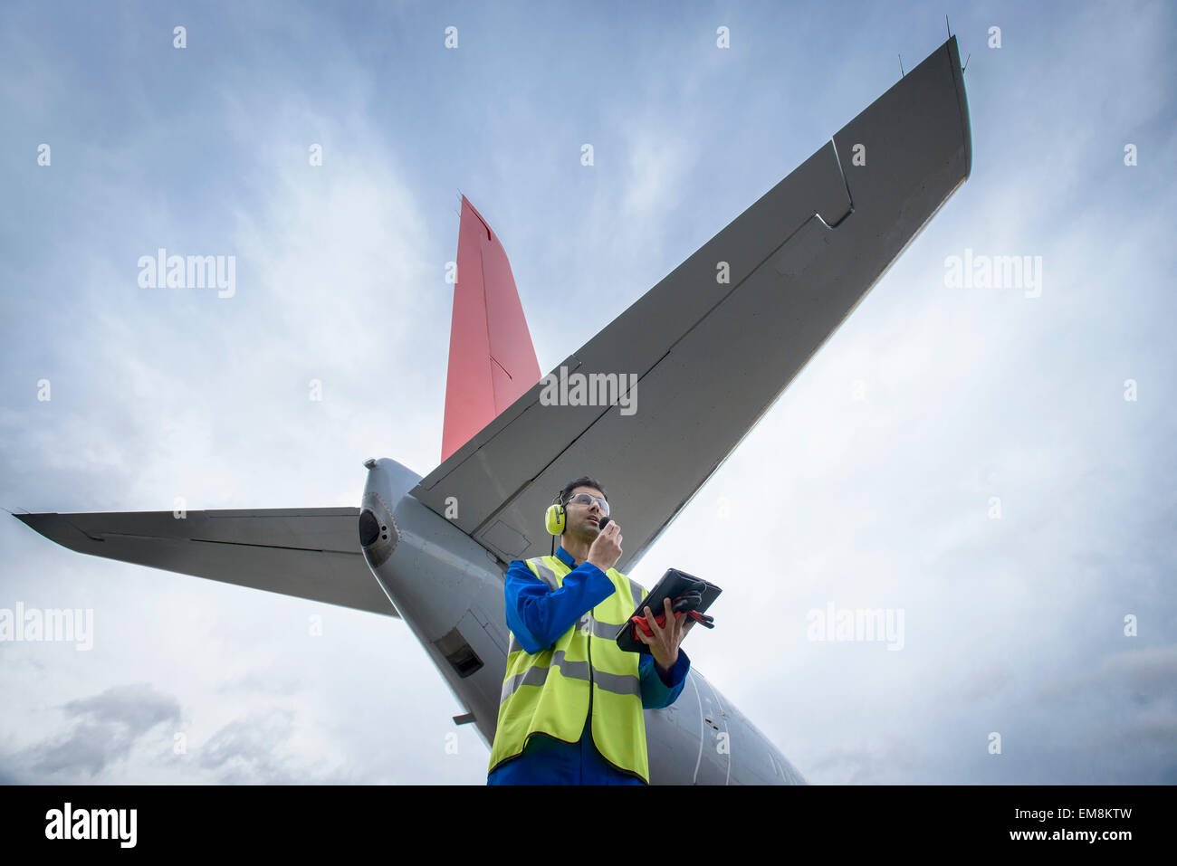 Airside engineer talking on radio near aircraft on runway, low angle view - Stock Image