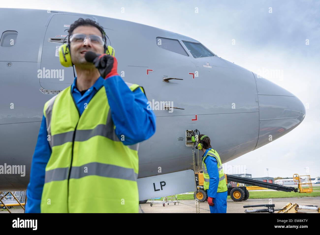 Airside engineer talking on radio near aircraft on runway - Stock Image