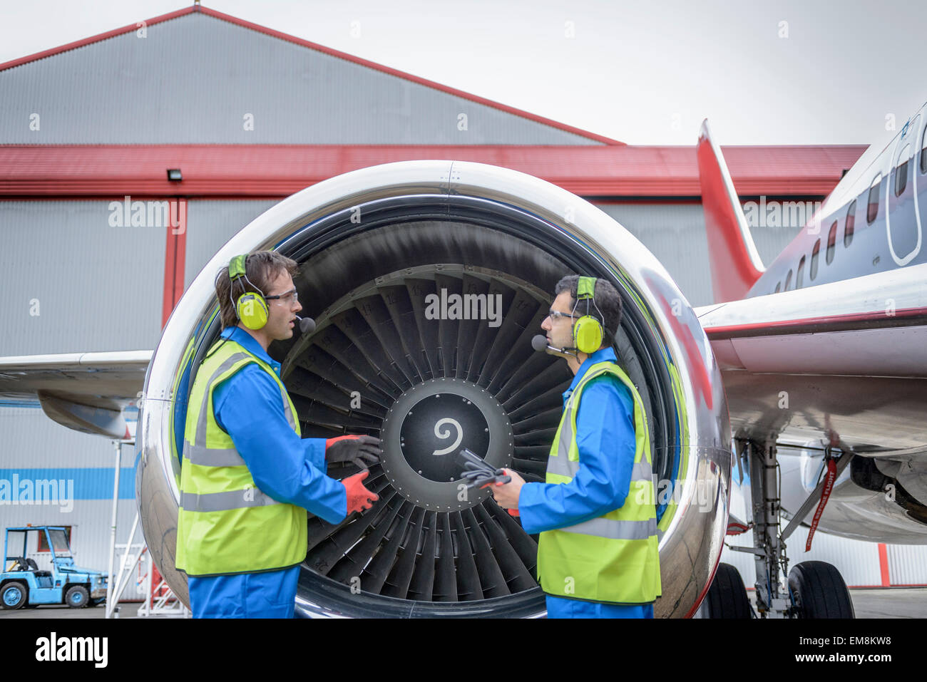 Airside engineers inspecting jet engine of aircraft - Stock Image